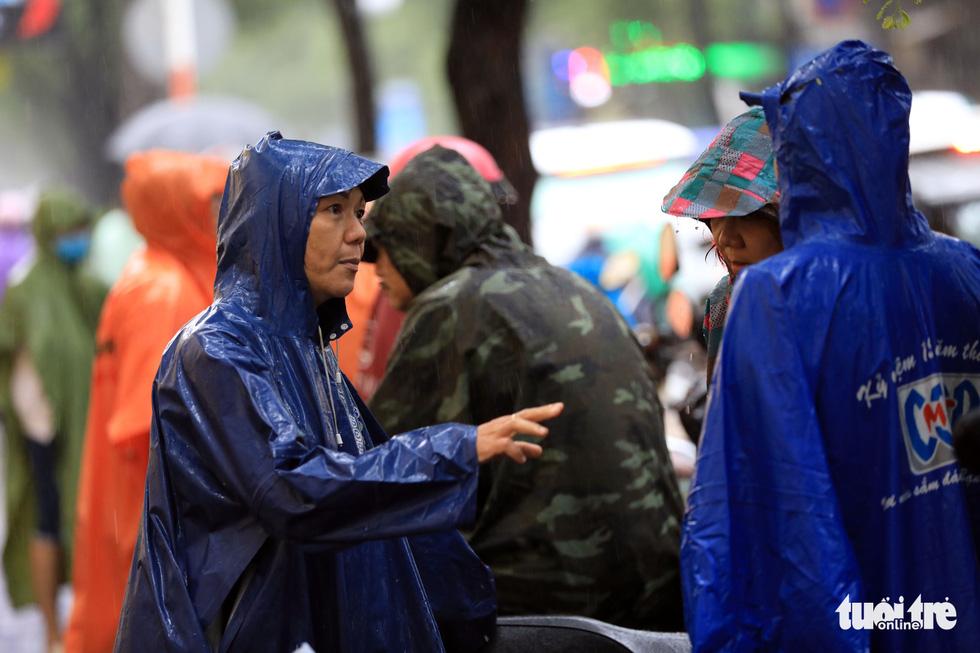 Mặc dù trời mưa nhưng các phụ huynh vẫn trao đổi về đề thi sáng nay - Ảnh: HỮU KHOA