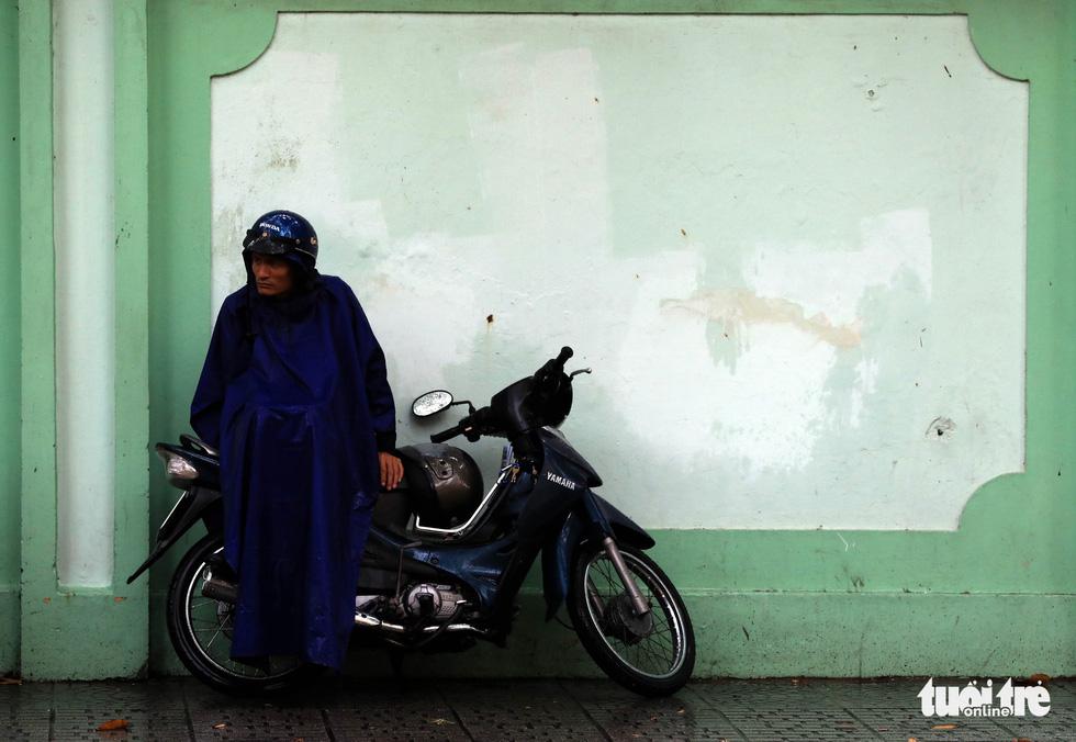Một phụ huynh co ro trong cơn mưa chiều để chờ con đi thi - Ảnh: HỮU KHOA
