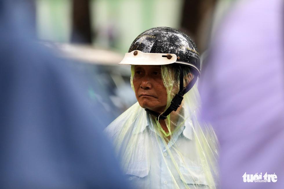 Chú Nguyễn Thanh Long đội mưa chờ con - Ảnh: HỮU KHOA