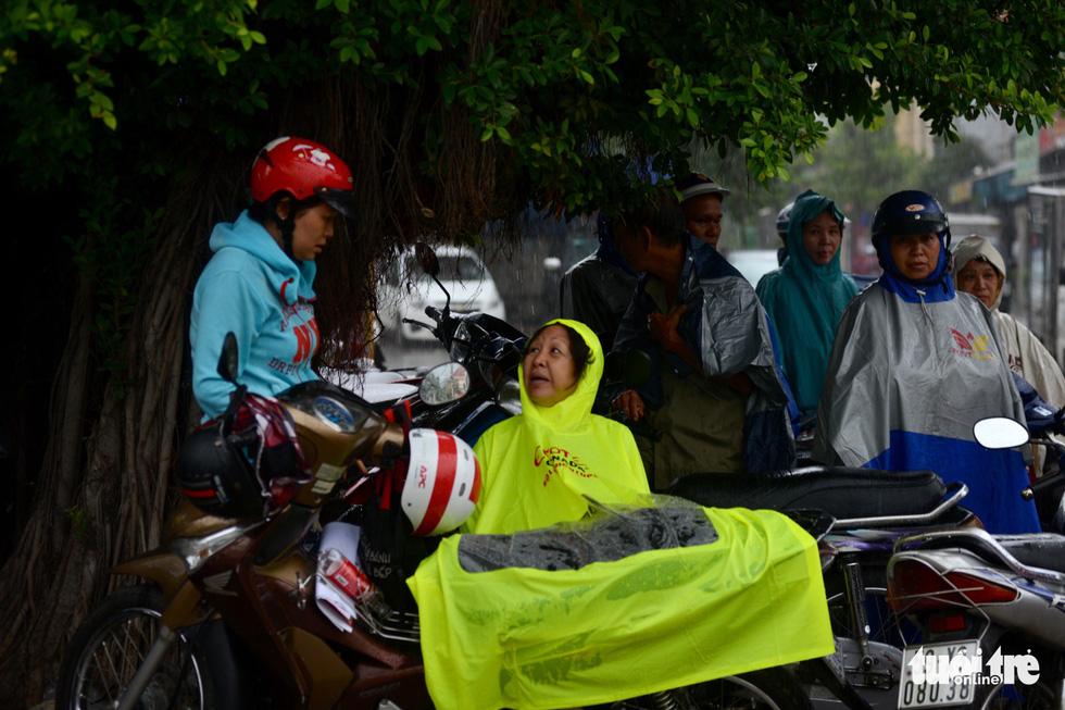 Cơn mưa chiều 26-6 bất ngờ đổ ập xuống khiến nhiều phụ huynh không kịp xoay sở. Dù vậy mọi người vẫn ráng nán lại chờ đến lúc con ra - Ảnh: DUYÊN PHAN