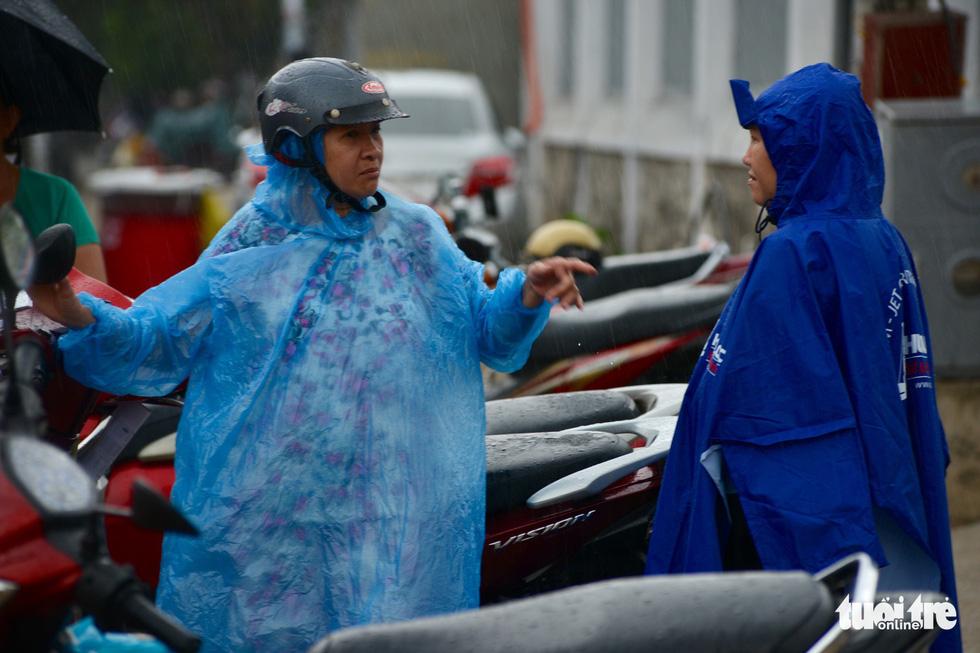 Trời mưa thì mặc trời mưa, nhiều phụ huynh mặc áo mưa đứng chờ sẵn để con ra không phải mất công tìm mình - Ảnh: DUYÊN PHAN