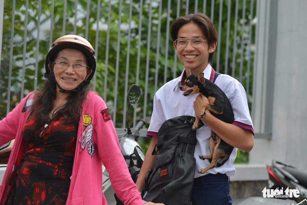 Em Lê Duy sau khi thi xong liền chạy ngay đến mẹ và ôm chú chó cưng của mình. Mẹ Duy tâm lý mang cả chó cưng của con tới hội đồng thi cùng chờ - Ảnh: DUYÊN PHAN