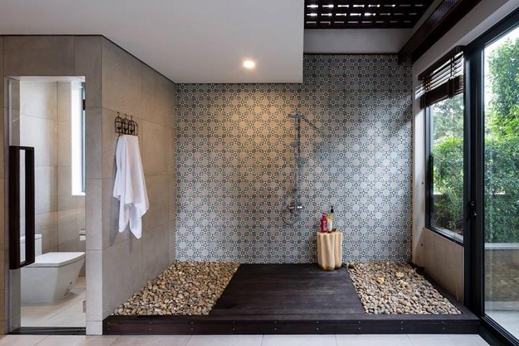 Phòng tắm thiết kế mở, sử dụng gạch bông ốp tường, trải sỏi dưới sàn.