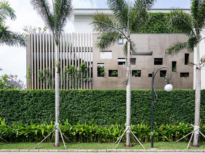 Bức tường rào bê tông thiết kế nhiều khoảng hở, giúp thông gió. Kế đến là hàng rào cây xanh được cắt tỉa gọn gàng.