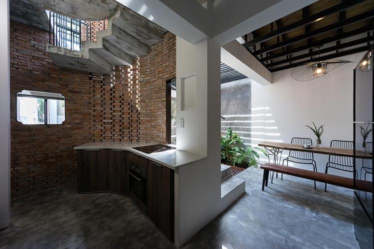 Tủ bếp thiết kế uốn theo bức tường gạch mộc.