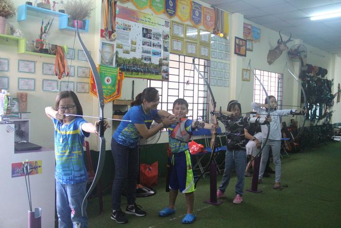 Nhiều bạn nhỏ chọn học bắn cung - một môn thể thao còn khá mới lạ ở Việt Nam trong hè này - Ảnh: MINH PHƯỢNG