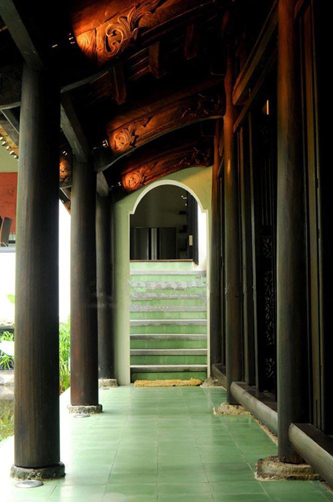 Lối đi vào được lát gạch màu rêu, có nhiều cột gỗ và phần mái che bằng ngói cùng những hình ảnh chạm khắc gỗ giúp người nhìn liên tưởng đến những ngôi nhà cổ Bắc Bộ.