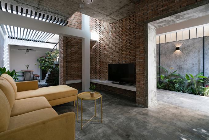 Ngôi nhà sử dụng kết hợp giữa các chi tiết tương phản: Những mảng tường gạch mộc xen kẽ tường sơn trắng, sàn bê tông với bàn ghế hiện đại.