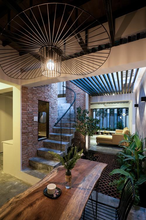 Khu bếp và bàn ăn nằm ở phía cuối nhà, tách biệt với phòng khách nhờ khoảng giếng trời.