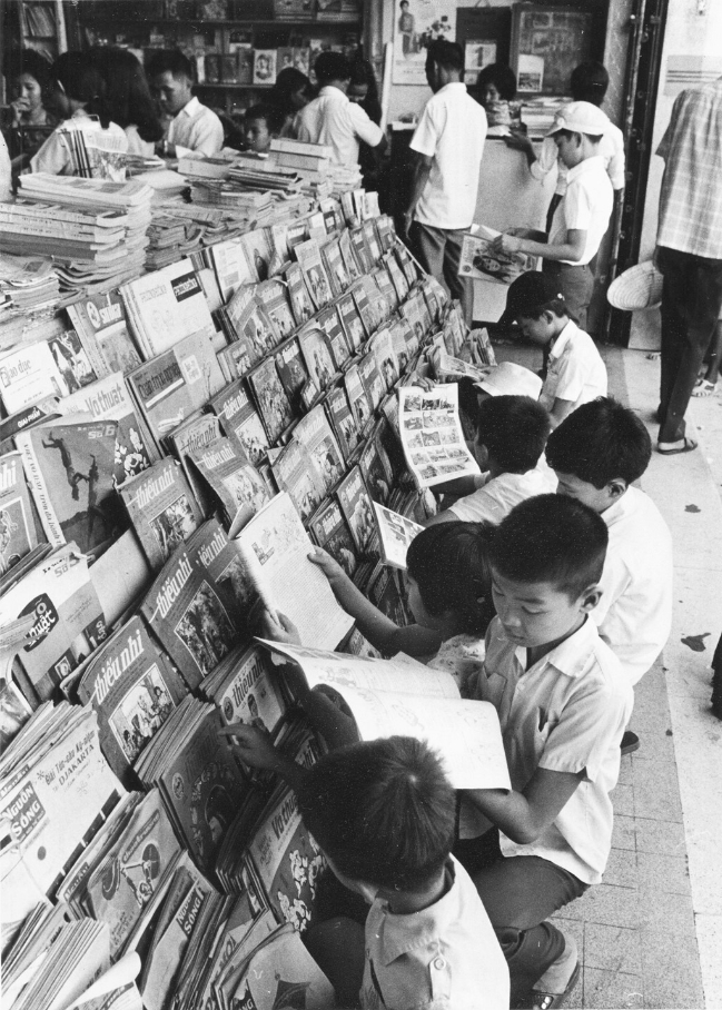 Trẻ em đọc báo Thiếu Nhi bên một sạp sách báo ở Sài Gòn