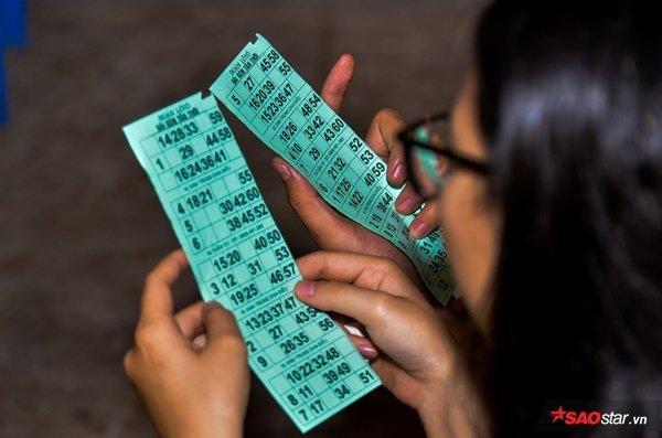 Chăm chú nghe hát, tìm số. Mỗi tờ vé dò như một chiếc vé đưa người trẻ Sài Gòn trở về với tuổi thơ.