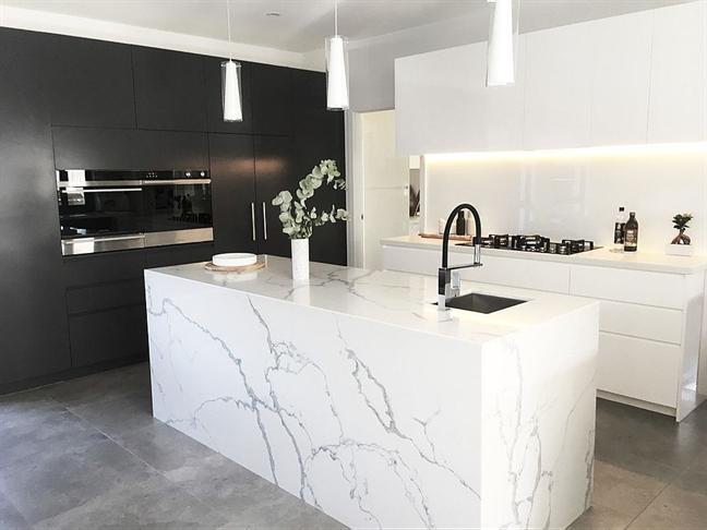 Sàn nhà bằng bê tông màu xám cũng làm nền nổi bật, hài hòa về màu sắc, chất liệu cho một nhà bếp cao cấp với chất liệu đá cẩm thạch trắng sang trọng cùng vách tường màu đen óng như than.