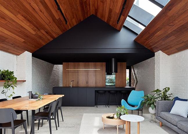 Một căn bếp hiện đại ở Melbourne gây ấn tượng nhờ trần mái gỗ, vách tường gạch nung, phết sơn trắng thô sơ mà không hề tráng thêm lớp xi măng nào. Ngoài ra, sàn nhà bê tông trắng xám hoàn toàn phù hợp, làm nền trang trí, đánh bật các thiết bị nội thất gồm bàn gỗ màu vàng trắng, ghế đen, xanh dương, chậu cây mini....
