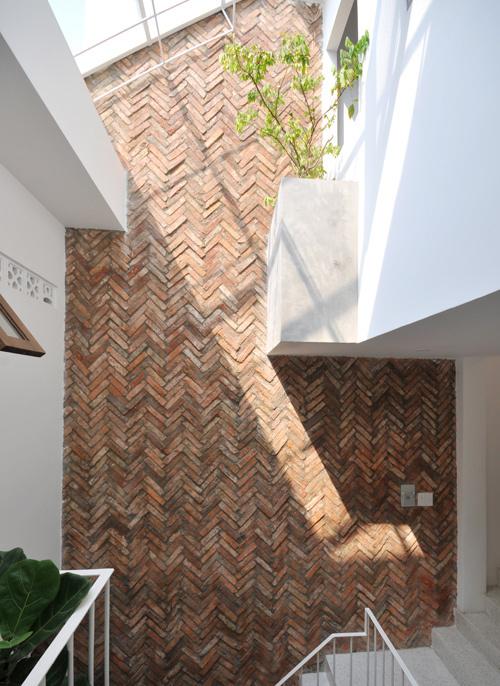 Mảng tường gạch xếp ở giếng trời đem lại cảm giác thân thuộc và tạo ấn tượng cho không gian sử dụng nhiều sắc trắng.