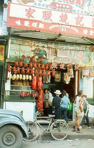 Tiệm lạp xường - thịt quay Trương Ký ở số 93 đường Phùng Hưng, Chợ Lớn năm 1965. Những tảng thịt đỏ chót và các dòng chữ tiếng hoa lớn màu đỏ là nét đặc trưng để nhận ra các cửa hiệu thịt quay từ xa. Ảnh tư liệu. Ảnh tư liệu.