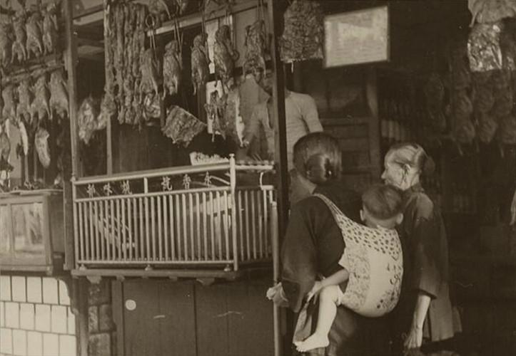 Bên ngoài một tiệm thịt quay ở Sài Gòn năm 1948. Những khu vực có đông người Hoa sinh sống cũng là những nơi tập trung nhiều cửa hàng thịt quay, như khu vực Chợ Lớn hoặc Chợ Cũ. Ảnh tư liệu.