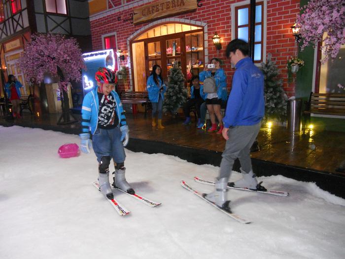 uỳnh Minh Tiến (12 tuổi) được huấn luyện viên hướng dẫn trượt ski - Ảnh: KIM ANH