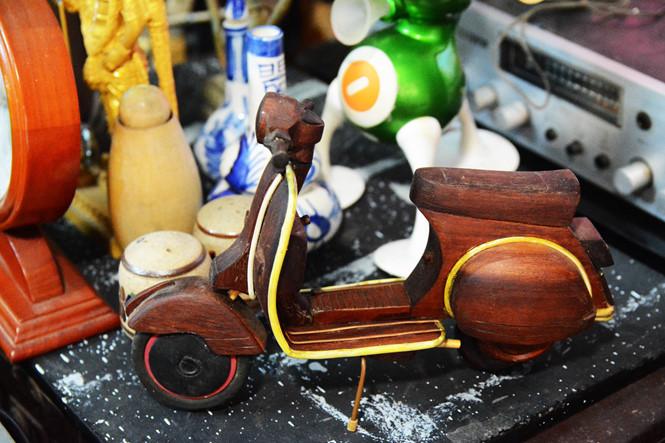 Không chỉ với các chất liệu sắt, nhôm, linh kiện điện tử... ông Thơm còn có thể đục đẽo gỗ, đá thành những hình thù đẹp mắt. Đó là những chiếc xe bằng gỗ cây gõ, mặt người bằng rễ tầm vông, hay hình thú vật, lọ hoa... ẢNH: HOÀI NHÂN