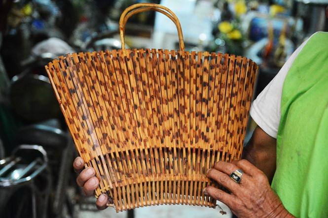 Chiếc giỏ bằng chất liệu cây tầm vông, có thể xếp dẹp gọn gàng. Ông Thơm cho biết, ông rất muốn mọi người dùng những chất liệu thế này để không gây ô nhiễm môi trường. ẢNH: HOÀI NHÂN