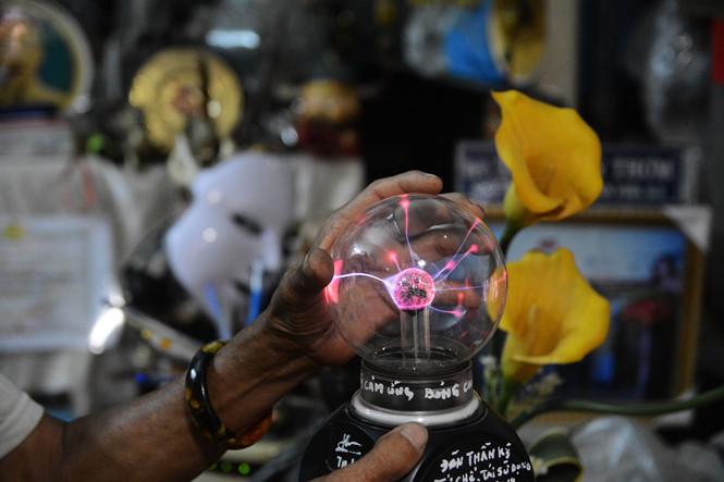 """Một trong những sản phẩm tái chế lạ lùng nhất của ông là chiếc đèn cảm ứng. Đế đèn được lấy từ đèn sạc, kết hợp linh kiện của ti vi. Chóa đèn là bóng cao áp, bên trong là giấy bạc. Tất cả đều được ông nhặt về khi đi gom rác. Khi bạn chạm tay vào, chiếc đèn sẽ """"búng"""" ra những tia sáng cực kỳ đẹp mắt và chuyển động khi ngón tay bạn di chuyển. ẢNH: HOÀI NHÂN"""