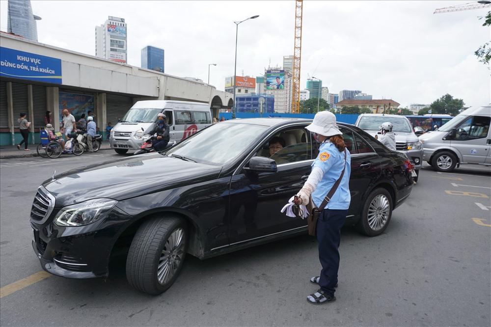 Nhân viên thu phí hướng dẫn cho xe ôtô vào đậu tại điểm đỗ xe ôtô có thu phí trên đường Phan Bội Châu (Q.1, TPHCM). Ảnh: MINH QUÂN