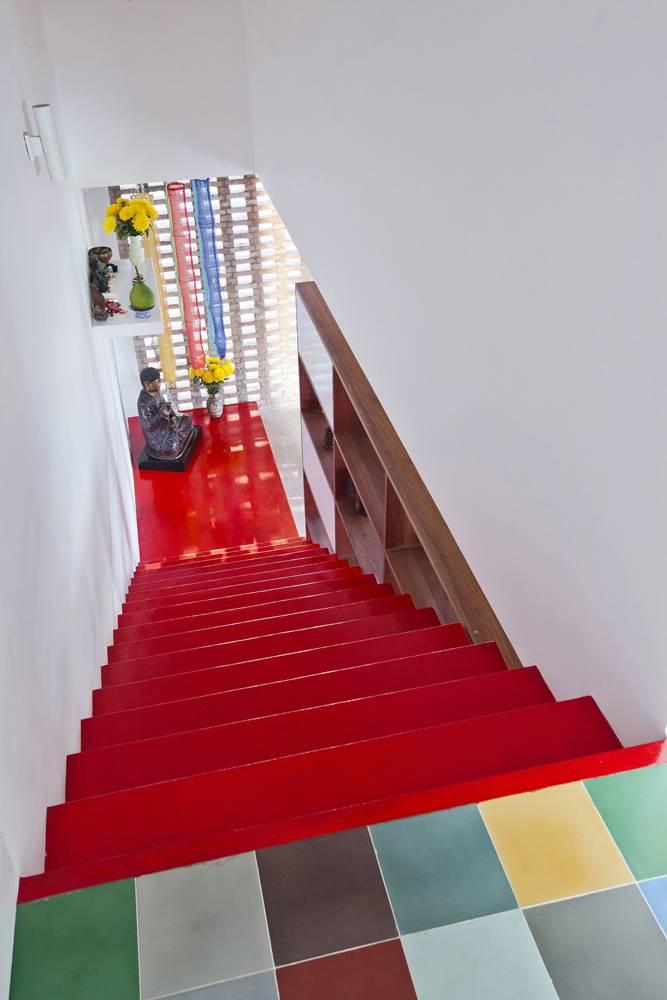 Những nhịp cầu thang đỏ mang lại hiệu quả thị giác cao, tương phản với gam màu lạnh của bê tông trần, sàn