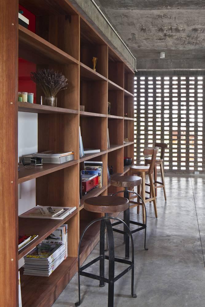 Mảng tường với gạch mộc được xây cách điệu tạo thành những lỗ thoáng giúp không gian phòng đọc sách, thư giãn ở tầng 2 trở nên sáng, mát mẻ và tĩnh tại hơn