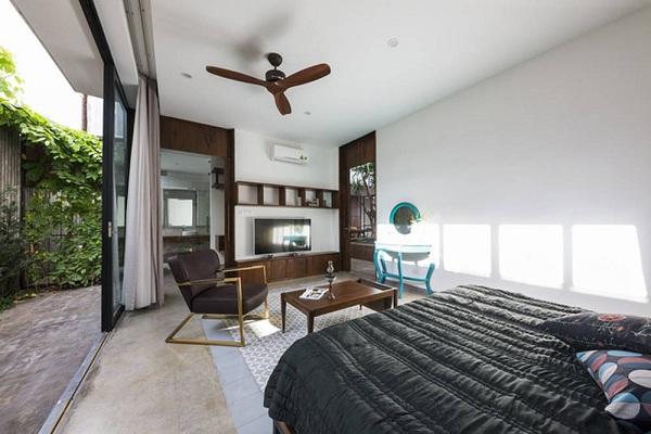 Phòng ngủ bên dưới tầng một có một cửa sổ trượt lớn tạo cảm giác cởi mở.