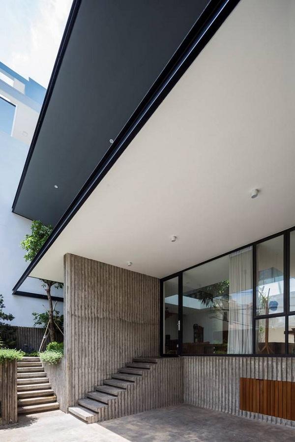 Mặt tiền căn nhà sở hữu một hiên lớn ngoài trời cho cả hai tầng, che nắng nhờ phần mái vươn ra.
