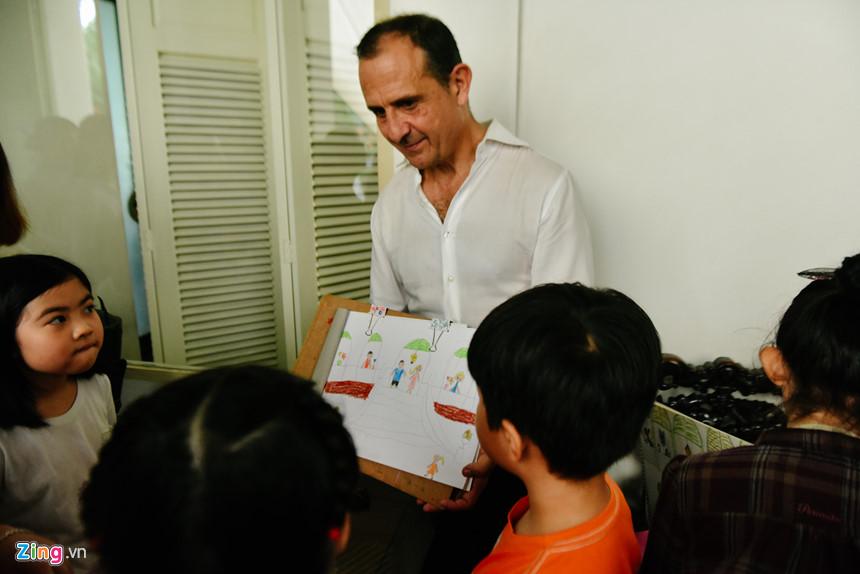 """Tổng lãnh sự Floreani xem tranh do các học sinh vẽ sau khi tham quan dinh thự. Ông trò chuyện bằng tiếng Anh với các em, khen từng bức tranh """"đẹp và sinh động""""."""