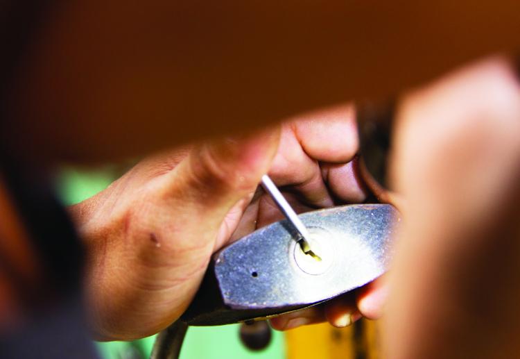 4-1Người thợ đang mở ổ khóa cho khách hàng.