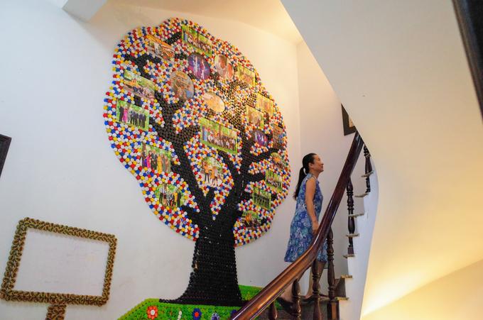 """Mô hình """"cây gia đình"""" được làm từ hàng nghìn nắp nhựa tạo nên điểm nhấn cho lối cầu thang. """"Mới đầu, tôi cũng hay cằn nhằn vì nhà cửa lúc nào cũng bừa bộn chai thủy tinh, nắp nhựa, nhưng rồi thấy chồng đam mê tái chế, tôi hoàn toàn ủng hộ"""", vợ ông chia sẻ."""
