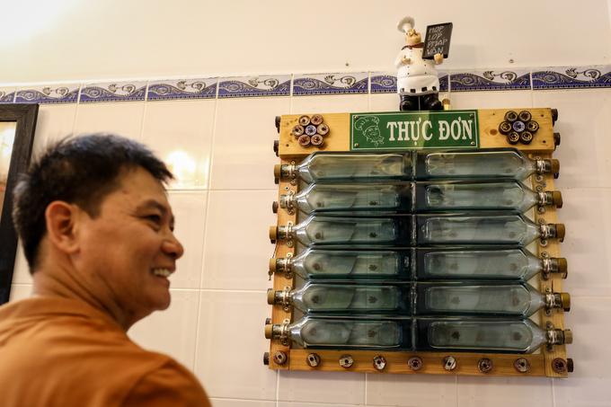 Góc bếp xinh xắn của gia đình ông Bình với kệ thực đơn hàng ngày làm từ những vỏ chai rượu và nắp nhựa.