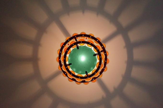 Chiếc đèn chùm được gắn những vỏ chai thủy tinh màu cam để tạo hiệu ứng bắt mắt. Ông Bình cho biết, để làm các vật dụng trong gia đình, ông thường chọn các loại chai dày, bền để đảm bảo độ an toàn.