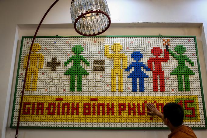 """Tại phòng khách, ông trưng bày bức tranh chủ đề gia đình được kết từ hơn 3.000 nắp chai nhựa.  """"Tôi vẫn thường nói với con cái là phải luôn tiết kiệm và có ý thức bảo vệ môi trường, thế nên nếu tận dụng được gì thì cứ tận dụng tối đa"""", ông giãi bày."""