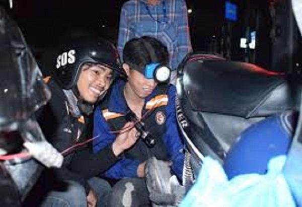 Các thành viên nhóm SOS Sài Gòn vá xe miễn phí cho người đi đường ở TP.HCM X.P