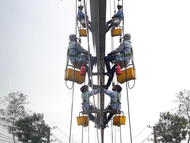 Nhiều người trẻ đã chọn Sài Gòn để mưu sinh. Trong ảnh, nhóm thanh niên đu dây lau kính các tòa nhà cao tầng ẢNH: XUÂN PHƯƠNG
