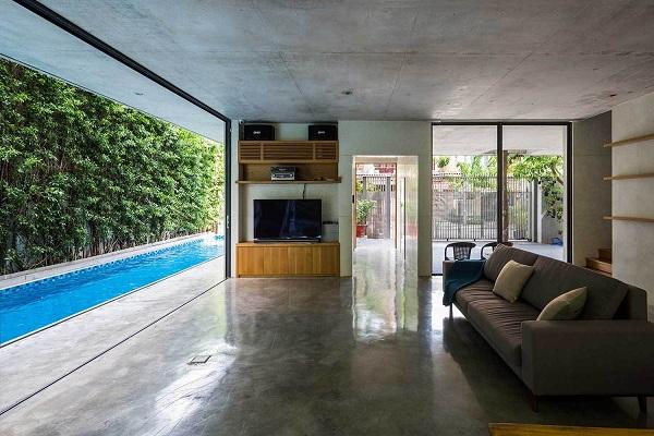 Không gian tầng 1 thoáng, rộng với khu vực bếp, khu ăn uống, phòng khách, hồ bơi và một bức tường cây xanh tuyệt đẹp.