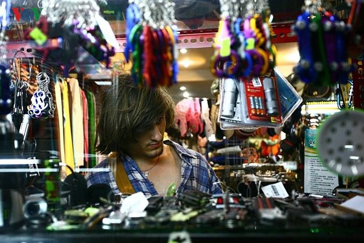 Một người khách đang chọn mua đồ trong một cửa hàng tạp hoá, đồ lưu niệm trên phố Bùi Viện.