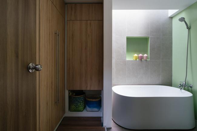Phòng tắm rộng rãi với bồn tắm lớn và tủ quần áo bằng gỗ.