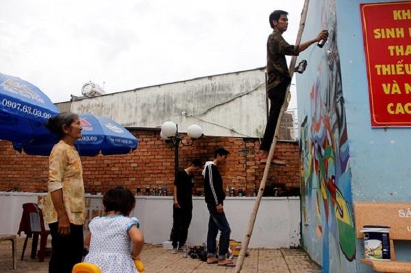 Bà Hà Thị Nhiều đứng quan sát nhóm bạn trẻ vẽ Graffti. Ảnh: THỤC QUYÊN