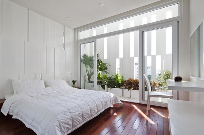 Phòng ngủ sáng với những khoảng trống để nắng rọi vào những chậu cây xanh mát gợi nhớ đến khu vườn tuổi thơ.